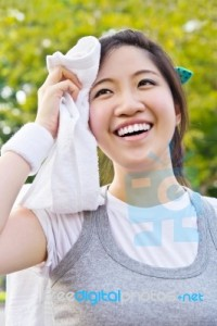 asian-woman-wiping-sweat-with-a-towel-after-exercising-100142787